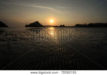 Sunset At The Seaside In A Low Tide When Bottom Of The Sea Is Visible And There Are Sand Stripes