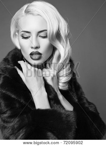 Portrait Of Sexy Woman With Blond Hair In Black Fur Coat