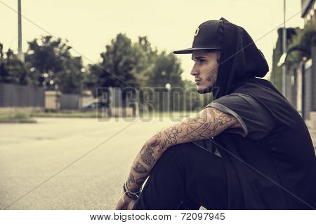 Attractive Young Man In City Sitting On Pavement