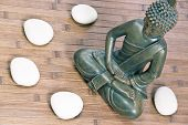 picture of siddhartha  - sitting buddha with white stones close up