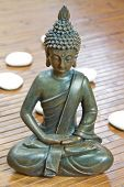 stock photo of siddhartha  - sitting buddha with white stones close up - JPG
