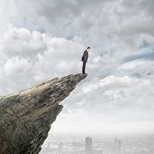 picture of edging  - Young businessman standing on edge of rock mountain - JPG