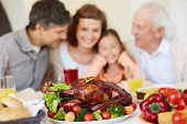 picture of turkey dinner  - Thanksgiving roasted turkey on holiday table and family of four on background - JPG