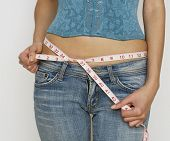 stock photo of bare midriff  - Young woman in blue jeans and bare midriff measuring her waist - JPG