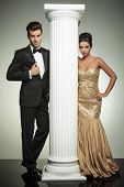picture of evening gown  - formal man and woman in evening clothes posing near column in studio - JPG