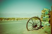 stock photo of wagon wheel  - old wagon wheel at death valley national park color toned - JPG