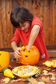 image of jack-o-lantern  - Boy busy carving a pumpkin jack - JPG
