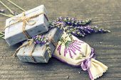 stock photo of sachets  - lavender soap and scented sachets with fresh flowers over wooden background - JPG
