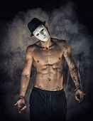 pic of shirtless  - Shirtless man dancer or actor with creepy scary mask on tilted head on dark smoky background - JPG