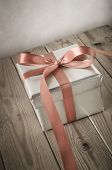 pic of gift wrapped  - Angled shot of a gift box with closed lid wrapped in silver paper and tied to a bow with a satin ribbon - JPG