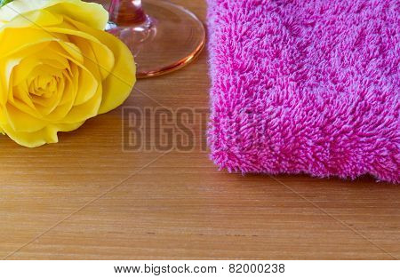 Yellow rose with a wine glass and a pink towel