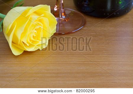 Yellow rose with a bottle of wine and a glass