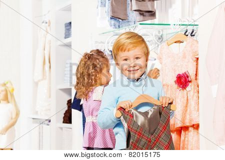 Boy with hanger and girl behind choosing clothes