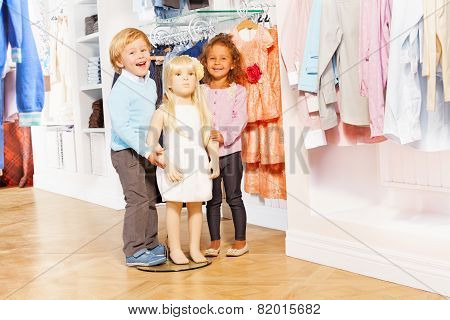 Boy and laughing girl stand with doll mannequin