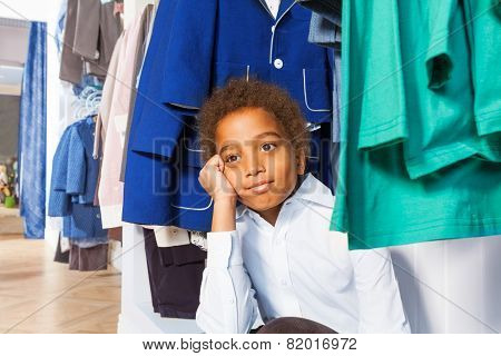 African boy with hand on cheek sits under hangers