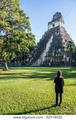 Young Girl Contemplating Mayan Ruins At Tikal, National Park. Traveling Guatemala, Central America.