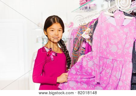 Asian girl with braid chooses clothes in shop
