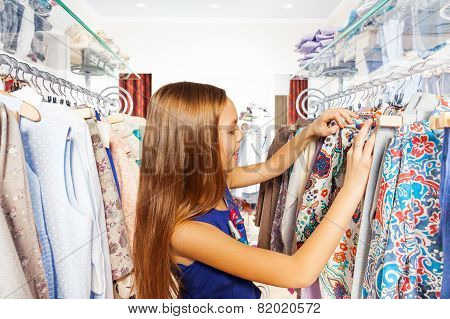 Happy girl searching for clothes during shopping