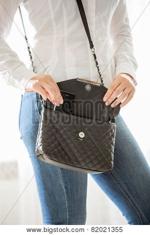 Young Stylish Woman Taking Cellphone Out Of Handbag