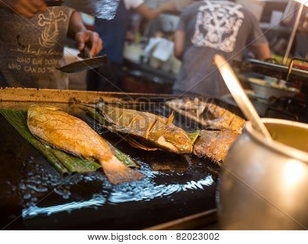 Man Grills Fish In Asian Restaurant