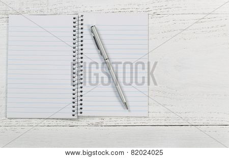 White Desktop With Notepad And Pen