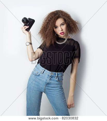 beautiful young hipster girl holding the camera makes images, photos on the camera, in jeans