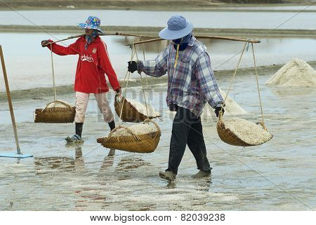 Women carry salt at the salt farm in Huahin, Thailand.