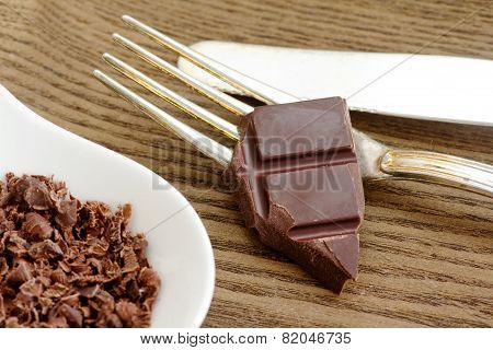 Slice Of Chocolate Bar Over Fork  With Chocolate Chips