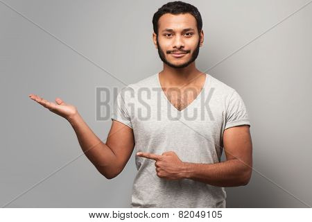 Young mixed race man pointing aside