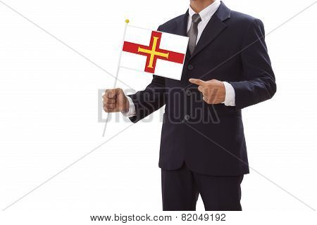 Businessman in suit holding Guernsey Flag