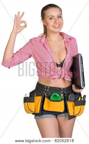 Woman in tool belt, with laptop under her armpit, showing okay sign
