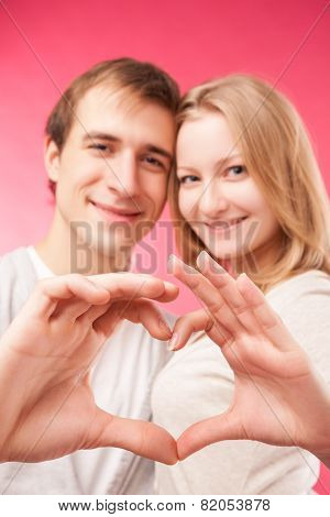 Couple making shape of heart by their hands