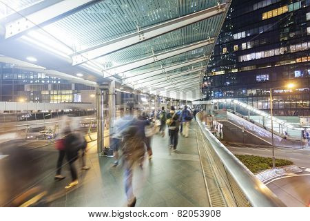 Commuters walking along an elevated walkway