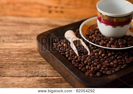 Cup With Plate On Tray Full Of Coffee Beans