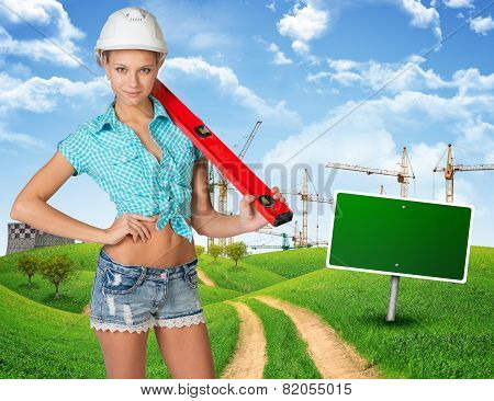 Woman in hard hat, holding large spirit level