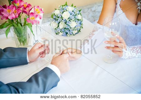Lovers Hold Hands While Sitting At A Table