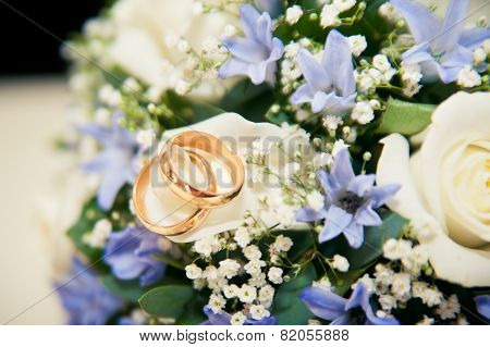 Wedding Rings Lie On A Bouquet