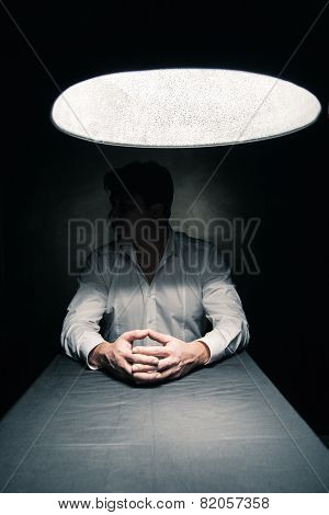 Man in a dark room illuminated only by lamp