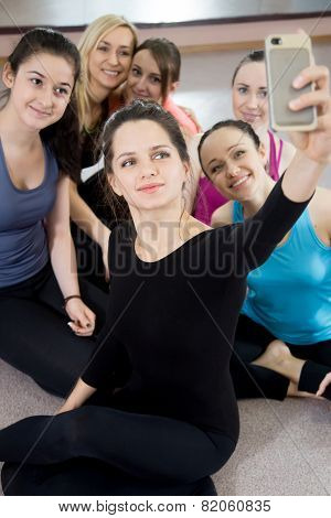 Group Of Beautiful Sporty Girls Posing For Selfie, Self-portrait With  Mobile Phone In Sports Gym