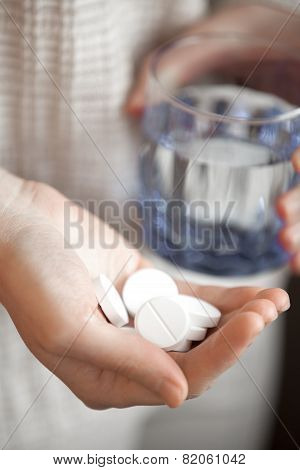Handful Of White Round Pills And Glass Of Water In Womans Hands