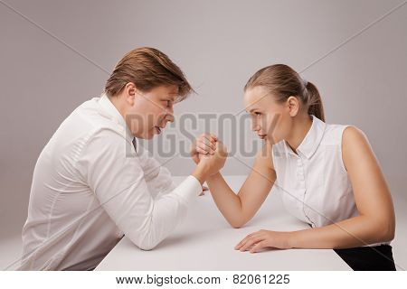 Man and woman in arm wrestling gesture