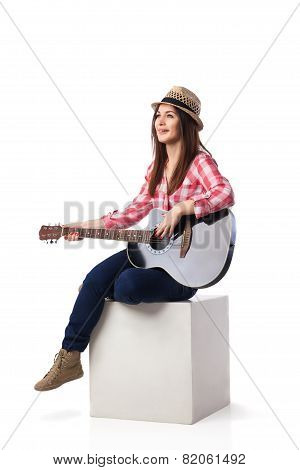 Woman is sitting and playing her guitar.