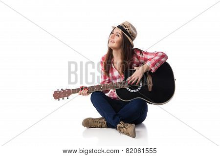 woman musician with guitar sitting on floor.