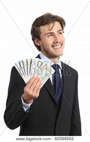 Happy Businessman Holding Money And Looking Sideways
