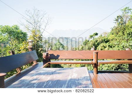 Outdoor Wooden Seating Area With Green Forest Scenery