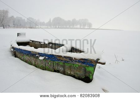 Old Wooden Used Boat Under Snow In Winter Near Lake And Fog