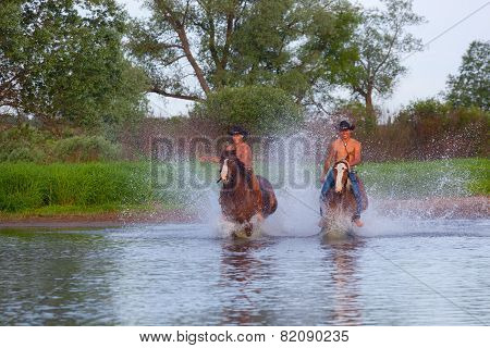 Two cheerful cowboys jump on horses through the river