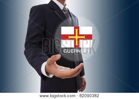Businessman hand showing Guernsey Flag