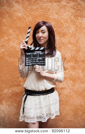 Young Woman In 70S Hippie Style Smiling With Clapperboard