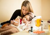stock photo of lie  - Young mother checking temperature of sick daughter lying in bed - JPG